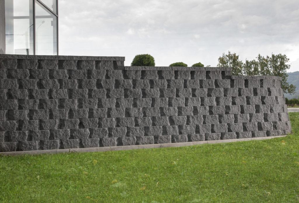 Mur oporowy z pustaków łupanych łukowo prefabrykowanych z gruntu zbrojonego CJ BLOK PBO-25-Ł grafit